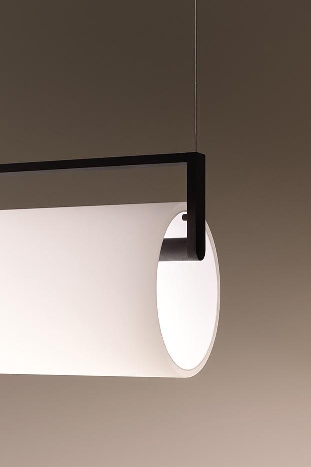 Detalle de la luminaria con un marco negro y un vidrio opalino soplado que refleja la luz