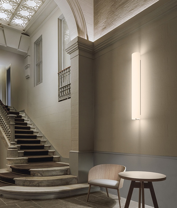 Otra imagen de la lámpara Kontur de pared, colgada en vertical, con el difusor de vidrio que genera una luz cálida