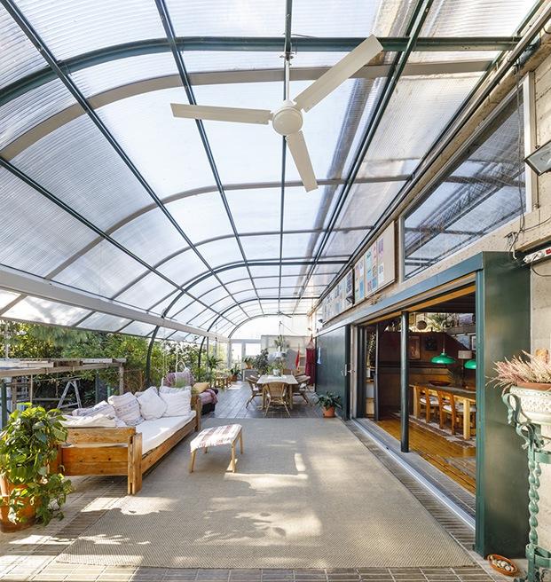 La casa se abre a una terraza cubierta con una pérgola