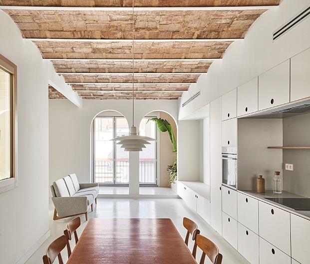 Desde el comedor y la cocina, vista de la zona de estar del salón con la galería al fondo, recuperada para el piso rehabilitado en Barcelona