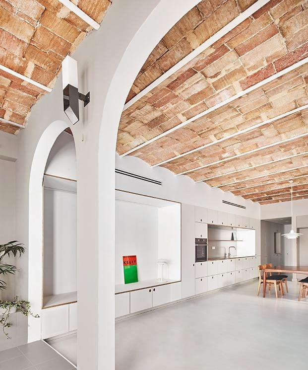 Desde la antigua galería unos arcos conducen al amplio espacio que acoge el salón, comedor y cocina de este viejo piso rehabilitado en Barcelona