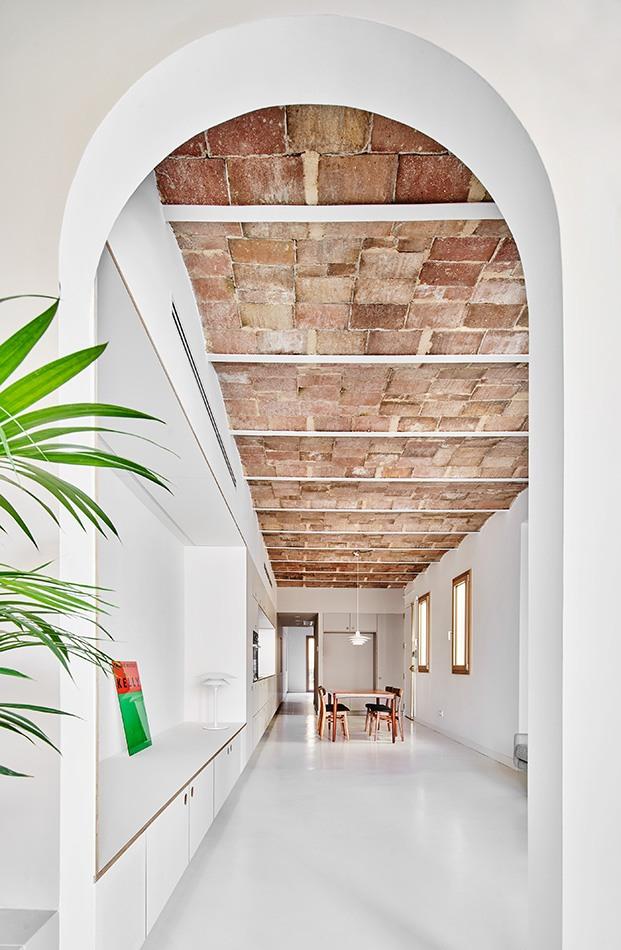 Uno de los arcos deja ver el techo original de bóveda catalana de ladrillo en Barcelona. AL fondo el comedor del piso rehabilitado  en Barcelona