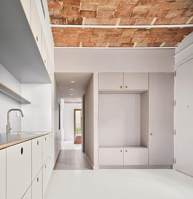 El módulo central, con muebles de Cubro Sahara mate, acoge la zona de almacenaje, instalaciones y el cuarto de baño. Al fondo el dormitorio