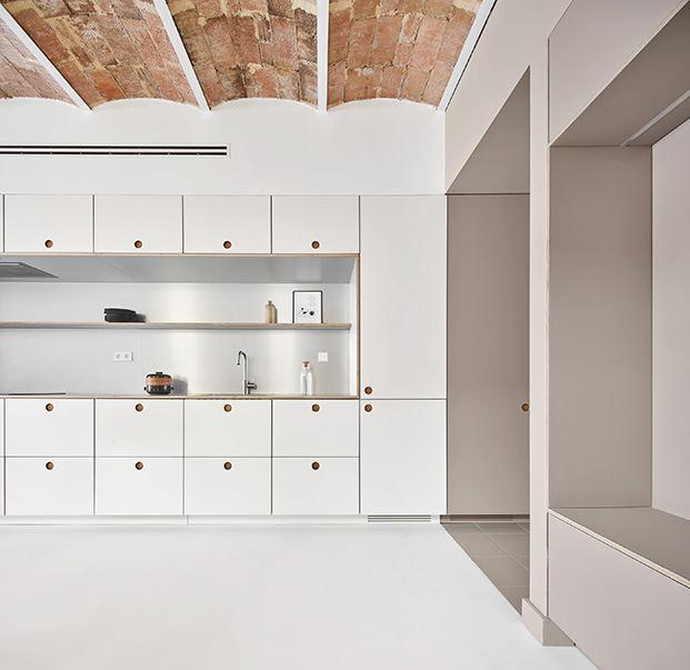 Muebles de Cubro realizados en dos tonos, blanco y Sahara mate delimitan la cocina y la zona de almacenaje y servicios