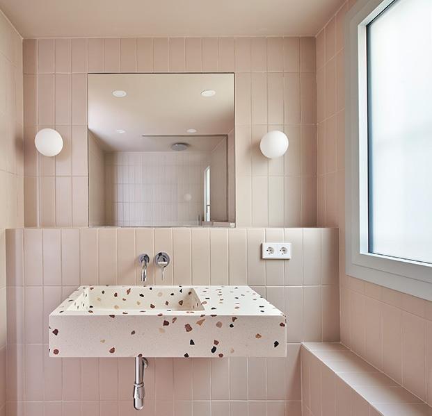 El cuarto de baño con un lavamanos de Huguet Mallorca con estampado de terrazo. Las baldosas se han escogido a tono con los armarios