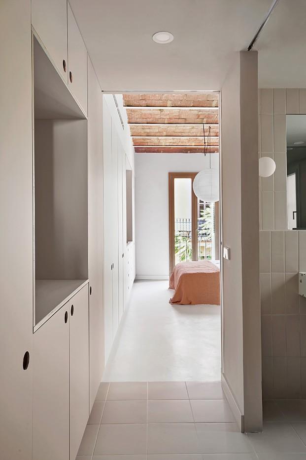 El pasillo conduce al cuarto de baño, realizado en el mismo tono beige que los muebles de almacenaje. Al fondo el  único dormitorio de este piso recién rehabilitado en el centro de Barcelona