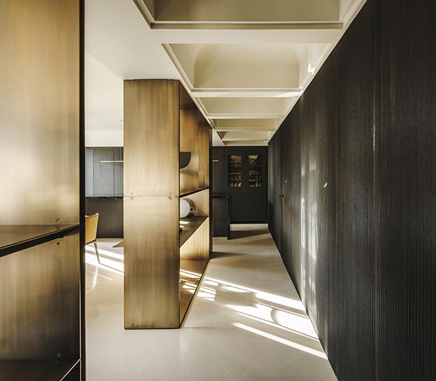 Madera teñida de negro para los armarios  y estanterías de latón dorado, todo diseño del estudio de Isabel López Vilalta