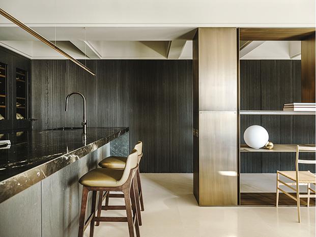 Vista de la cocina de Bulthaup conectada  con el salón a través de una estantería de latón, al fondo, aramrios de madera teñida en negro