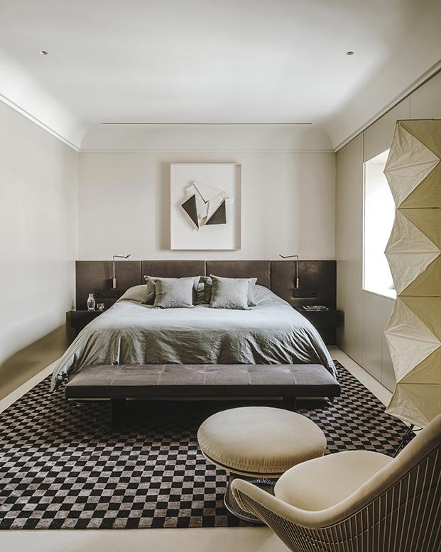 Vista de la zona de dormir del dormitorio principal  presidido por una obra de Manuel Ballesteros y un cabecero de piel hecho a medida