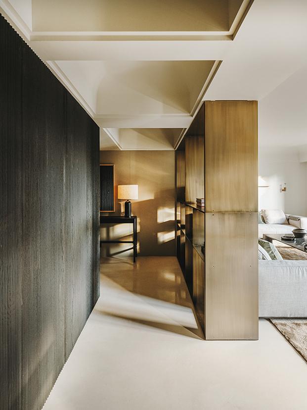 Una estantería de latón diseño del estudio de Isabel López Vilalta aisla el salón de la zona de entrada