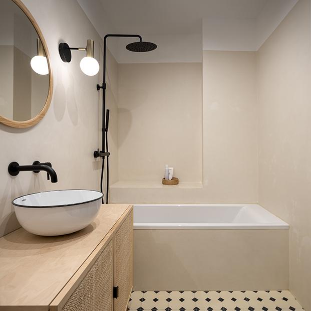 Otro de los baños con suelo de damero y griferías en negro a juego