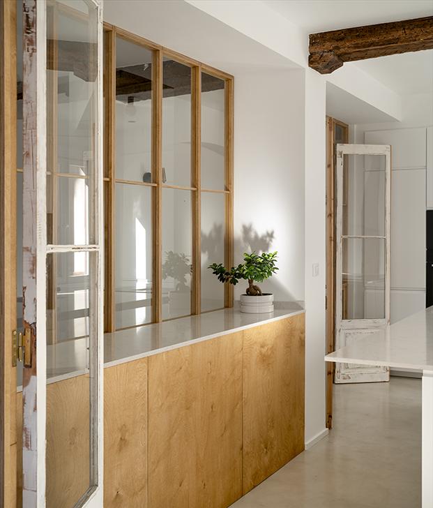 La cocina recibe la luz del salón a través del cerramiento de cristal y madera