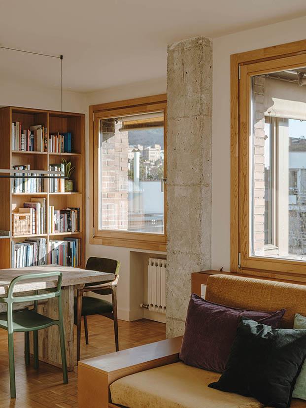 Se han repicado los muros de hormigón para dejarlos vistos, en la reforma del ático en Sarrià. Además, algunos muebles del salón, se han realizado a juego.