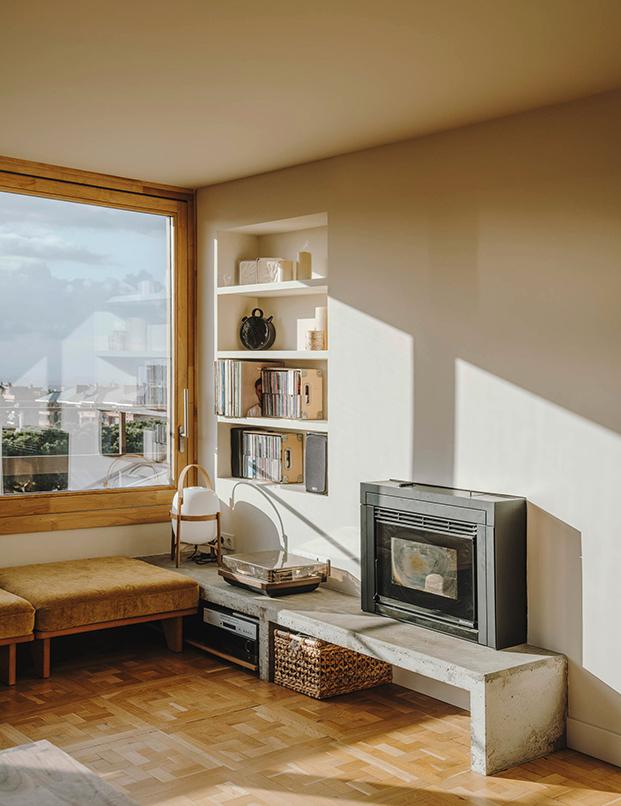 Un mueble de hormigón acoge una estufa de pellets que sustituye a la antigua chimenea, tras la reforma del ático en Sarrià.