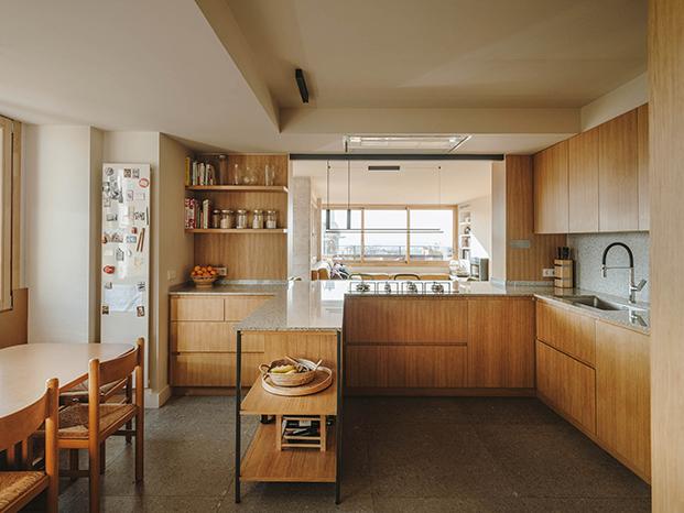 La cocina, toda en madera con muebles de madera y encimera de granito blanco cristal.