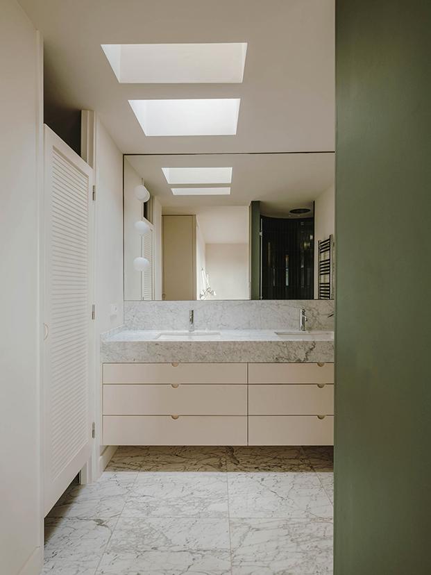 El cuarto de baño del dormitorio principal, en blanco y verde, se ha integrado  tras la reforma en la habitación principal del ático en Sarrià