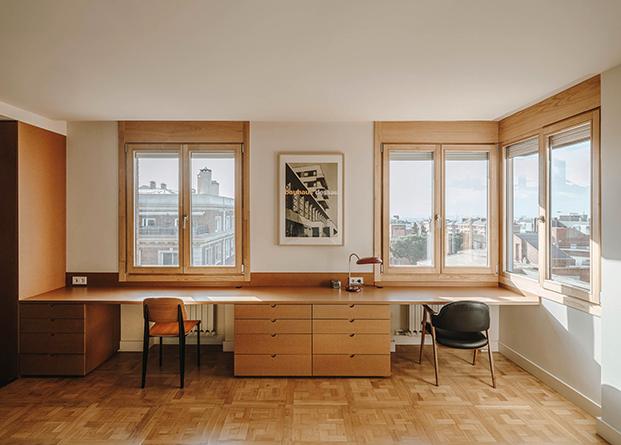 Un escritorio hecho en DM junto a las ventanas permite trabajar desde la misma habitación al tiempo que se disfrute de luz y vistas