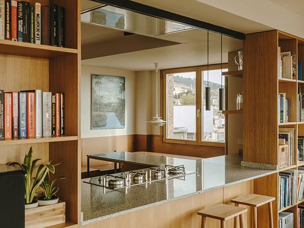 Un mueble de roble comunica los distintos ambientes del ático en Sarrià. Por la parte del salón forma una práctica estantería