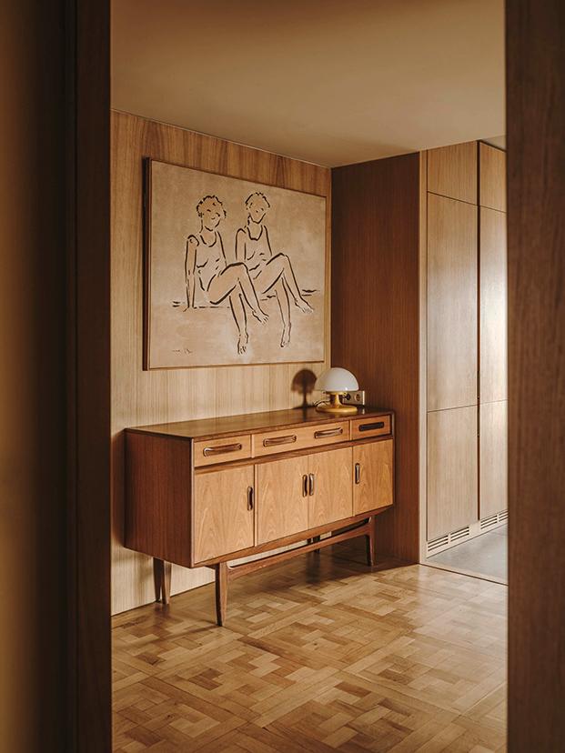Vista del recibidor con muebles vintage y paredes paneladas.