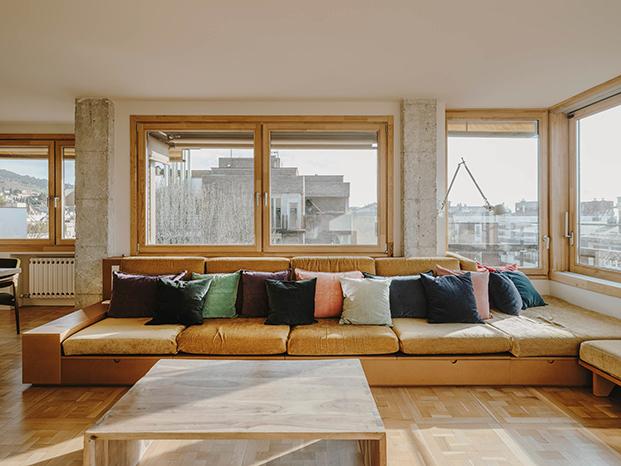 El sofá, realizado a medida permite ampliar su espacio con módulos y pufs. Las mesas son de hormigón hechas a medida