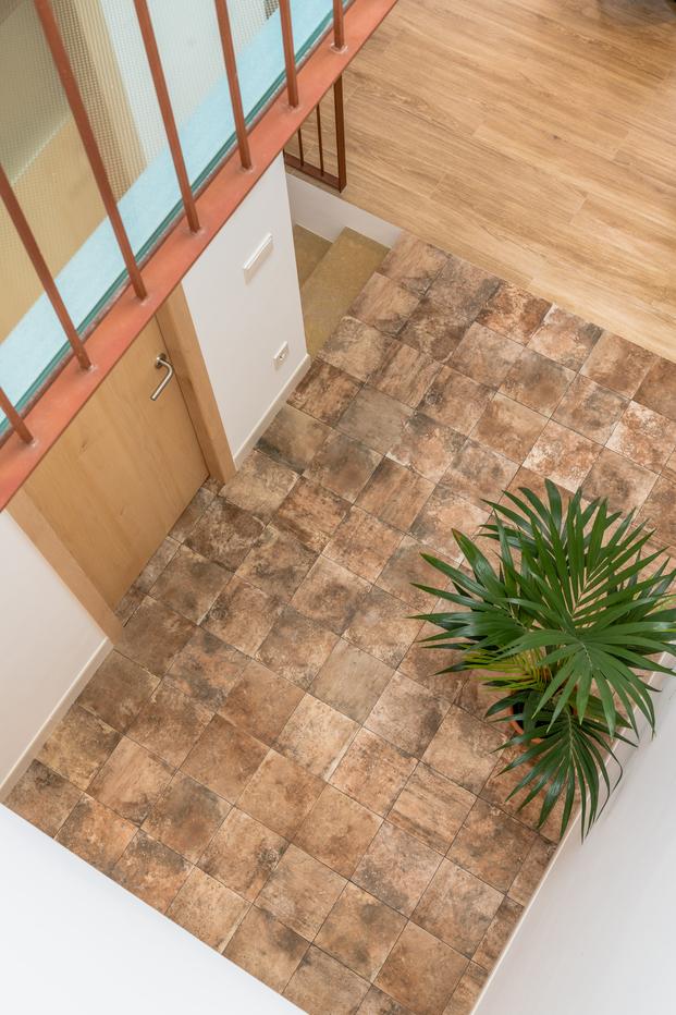 Una cocina turquesa, una claraboya y escaleras de hierro. Casa HE en Mahón de Líniarquitectura. Patio interior