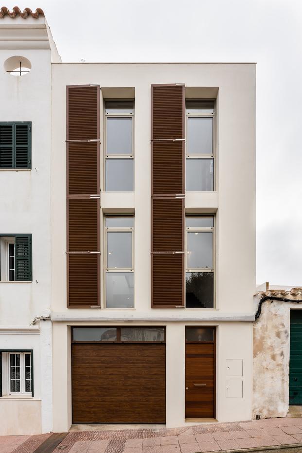 Una cocina turquesa, una claraboya y escaleras de hierro. Casa HE en Mahón de Líniarquitectura. Fachada