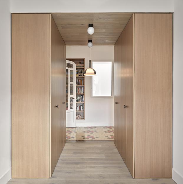 Vista de la zona de armarios en roble natural, y al fondo la estanteria diseñada a medida para el ático en Ruzafa