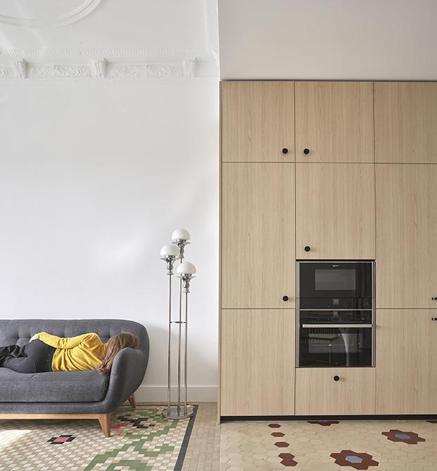 La zona de estar del salón, decorada con lámparas vintage y un sofá gris, comparten el mismo espacio diáfano que acoge al comedor y la cocina