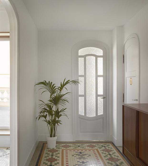 Las elegantes puertas curvas con cuarteros de cristal blancos son otras de las grandes protagonistas de este ático en Ruzafa
