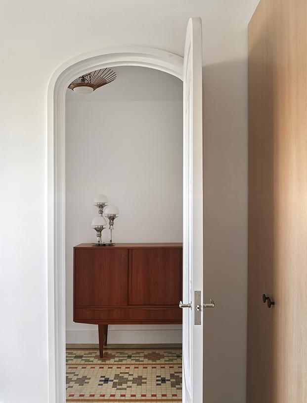 Las puertas en forma de arco dejan ver los muebles vintage que personalizan este ático en Ruzafa