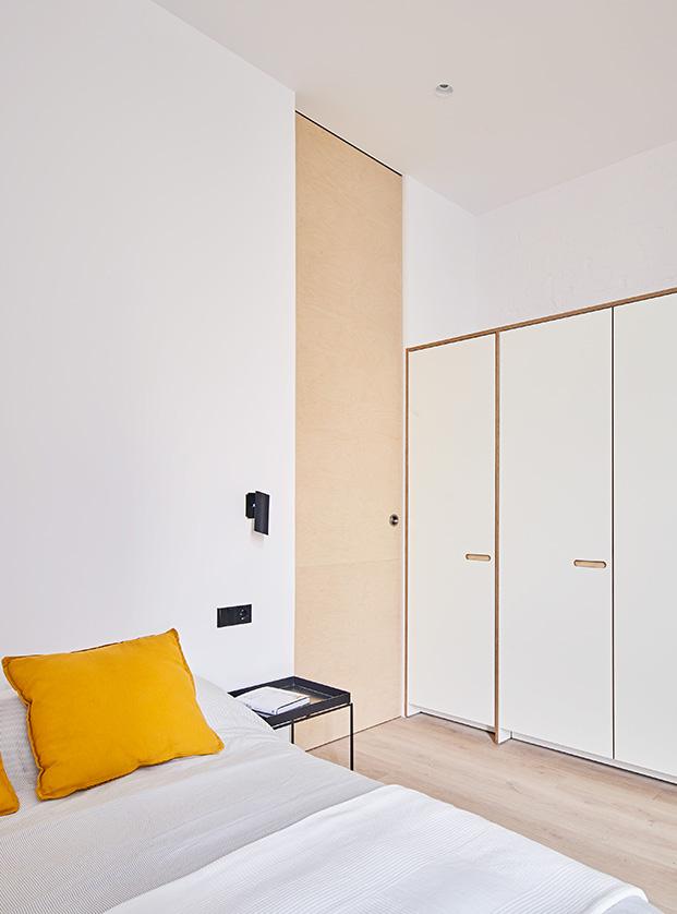 Una puerta corredera de grandes dimensiones separa el dormitorio de la zona de salón, comedor y cocina