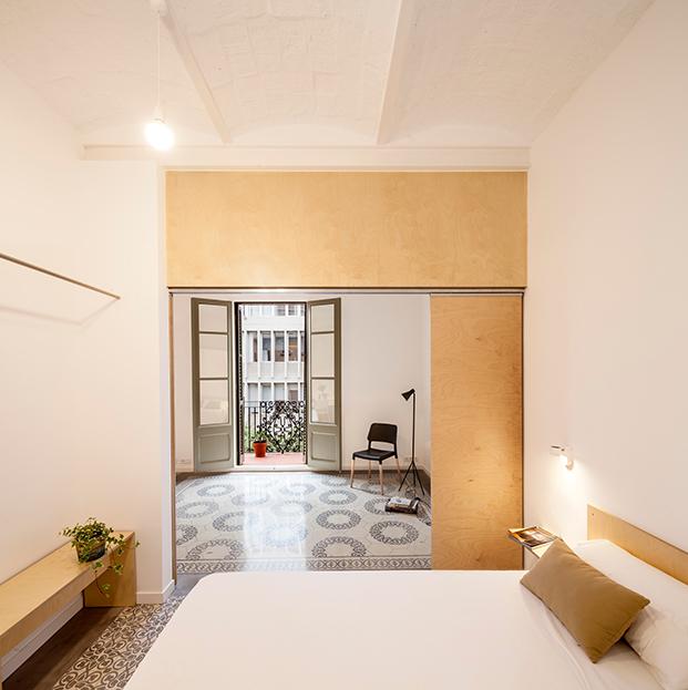 Desde el interior del dormitorio del apartamento del Eixample, vista del salón y el único balcón que da luz a la casa
