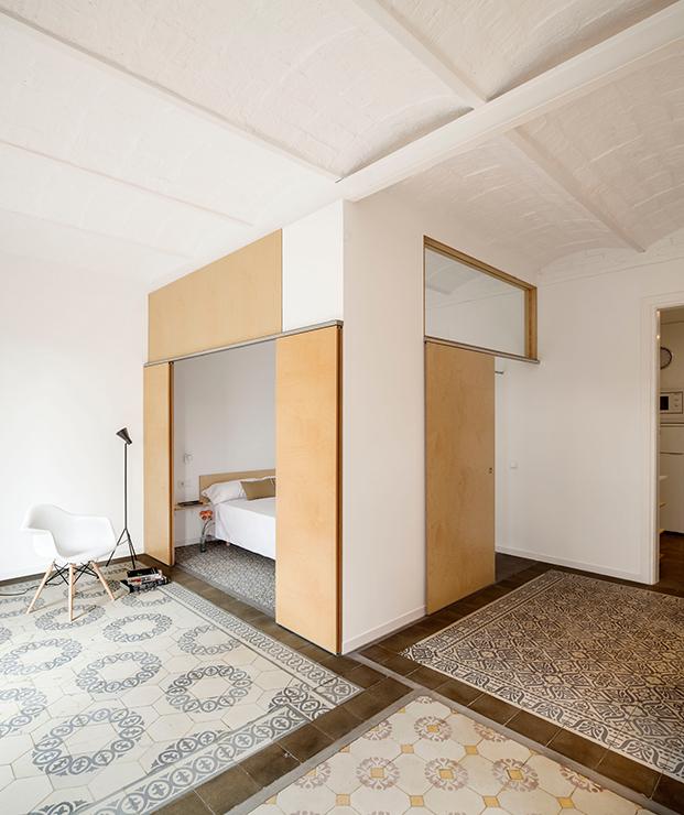 Espacios conectados por el suelo y puertas correderas con la parte alta de cristal para dar luz en el Apartamento del Eixample