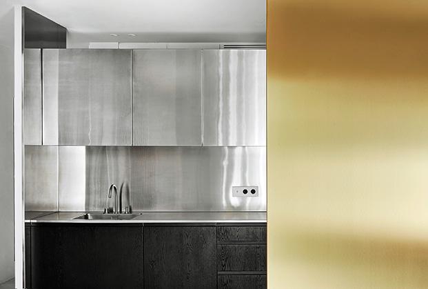 La cocina con muebles de roble y otros superiores de acero inoxidable, en primer término la columna dorada