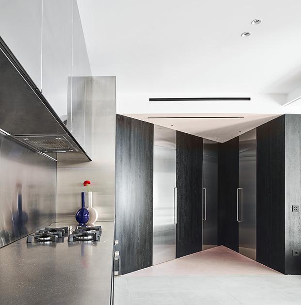 Vista de la cocina en acero inoxidable al igual que las puertas que dan paso a los dormitorios