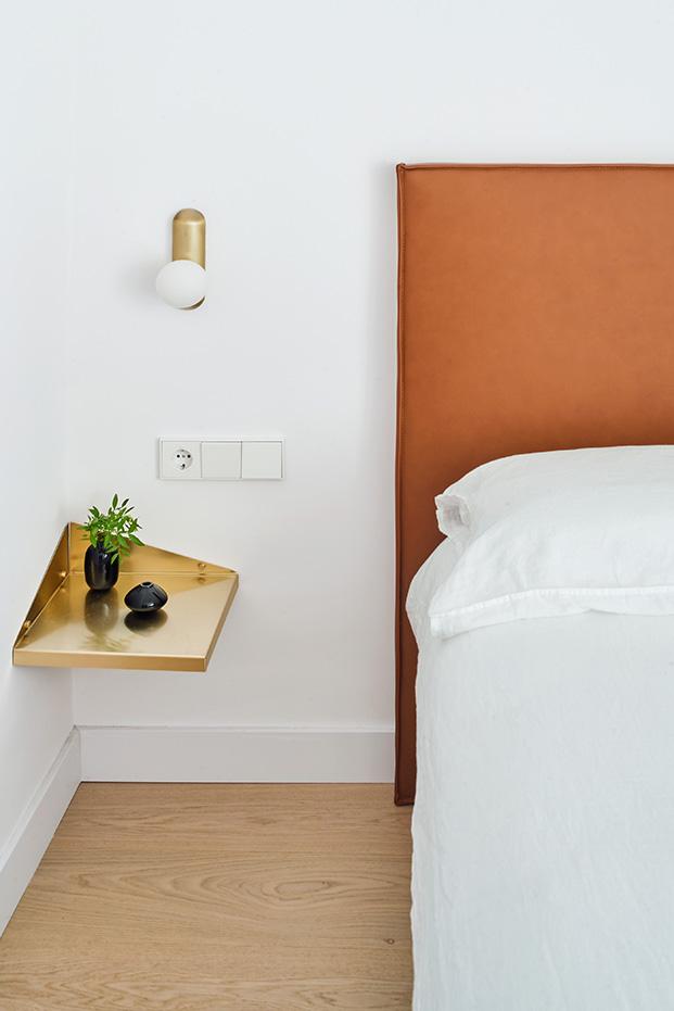 Dormitorio principal con la cama con un cabecero de piel natural de RSA y mesillas de latón diseño de la misma firma, las lámparas de latón son de Metalware