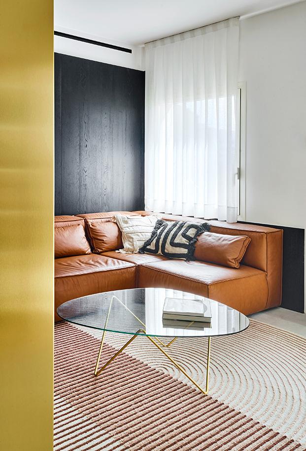Vista de una zona de estar del salón con un sofá diseño del estudio del arquitecto