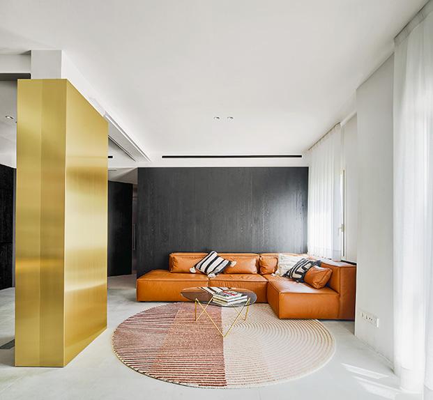 La columna aisa la zona de estar en la casa del arquitecto Raúl Sánchez, la mesa es de Gubi y la alfombra de Mut Design para Gan Rugs