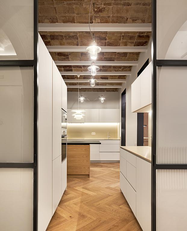 Vista de la cocina con mobiliario blanco y suelo de parqué colocado en espiga