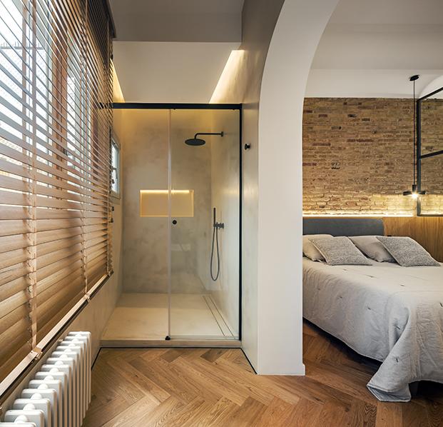 Vista del dormitorio principal del antiguo piso en Barcelona realizado en suite con zona de ducha y lavabo incorporada