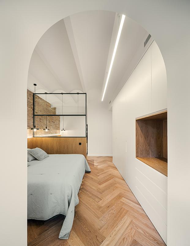 Madera, ladrillos y perfiles metálicos negros para el dormitorio principal