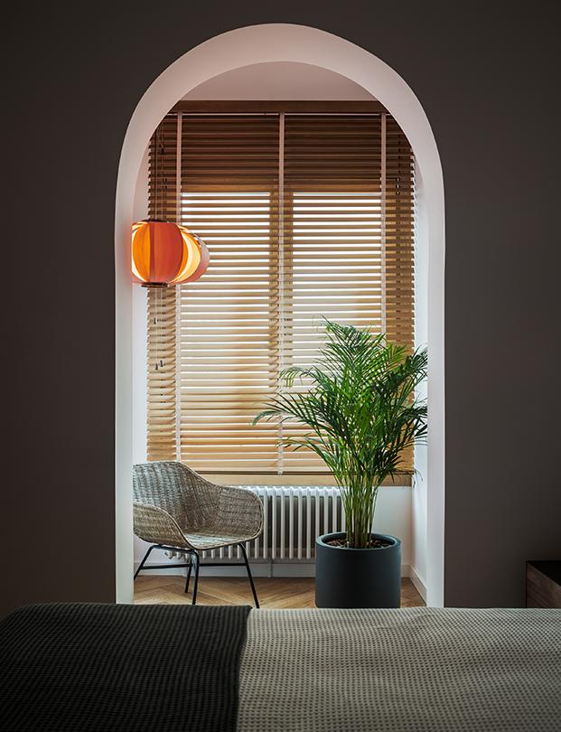 La zona de estar y lectura de uno de los dormitorios protagonizada por una lámpara Coderch