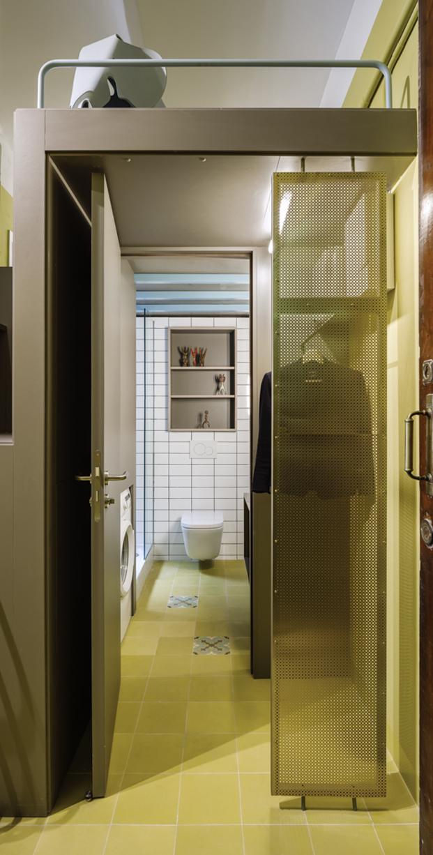 El baño, una zona de armarios y el altillo en el techo con una silla Elephant Eames de Vitra en este apartamento de 60 m2 en Barcelona