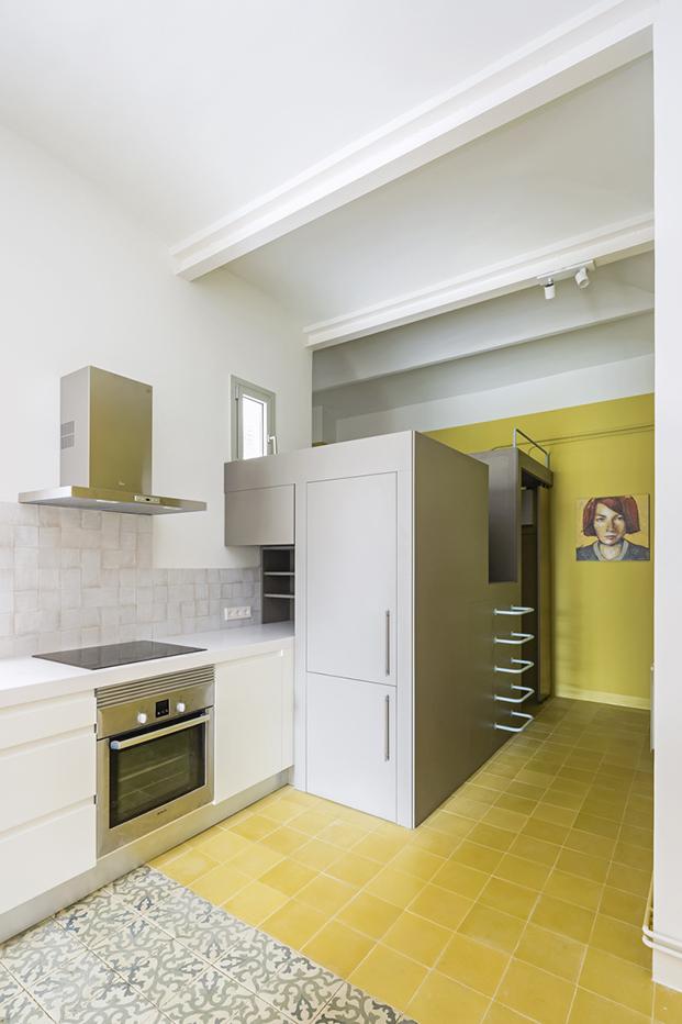 Una pieza en forma de cubo acoge parte de la cocina, la zona de almacenaje y el cuarto de baño. Unas escaleras permiten subir hasta el techo convertido en un altillo
