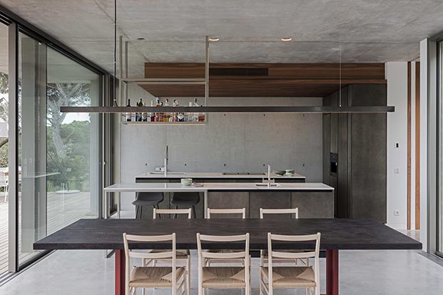 Vita del comedor y la cocina que se abren al exterior. La mesa de Lema se rodea con las míticas sillas Superleggera de Gio Ponti que edita Cassina