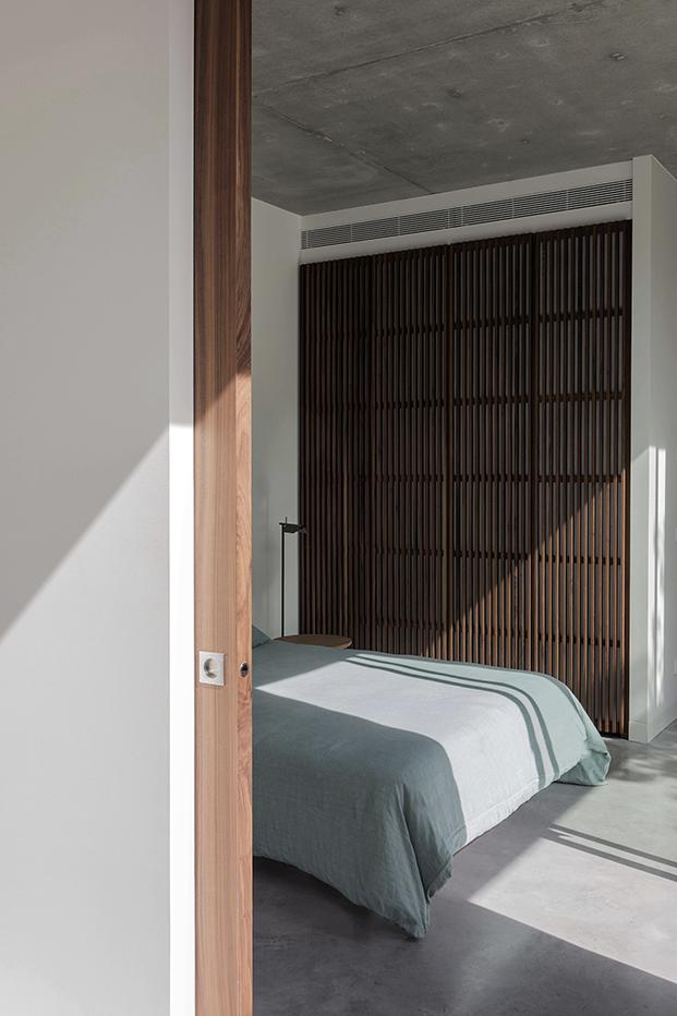 Aramrios panelados  y suelo de hormigón en uno de los dormitorios de esta casa brutalista en la costa brava. Las mesillas de noche son de Fredericia