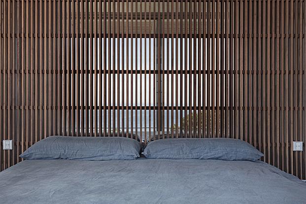 Unos paneles verticales delimitan abren el dormitorio a la terraza y las vistas al Mediterráneo