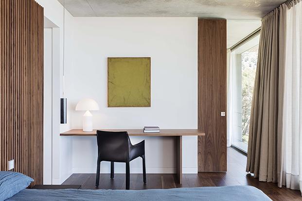 Este dormitorio cuenta con una zona de trabajo en la que destaca  la lámpara Atollo de Vico Magistreti que edita Oluce y sobre ella una obra de arte de Antonio Ferrer.