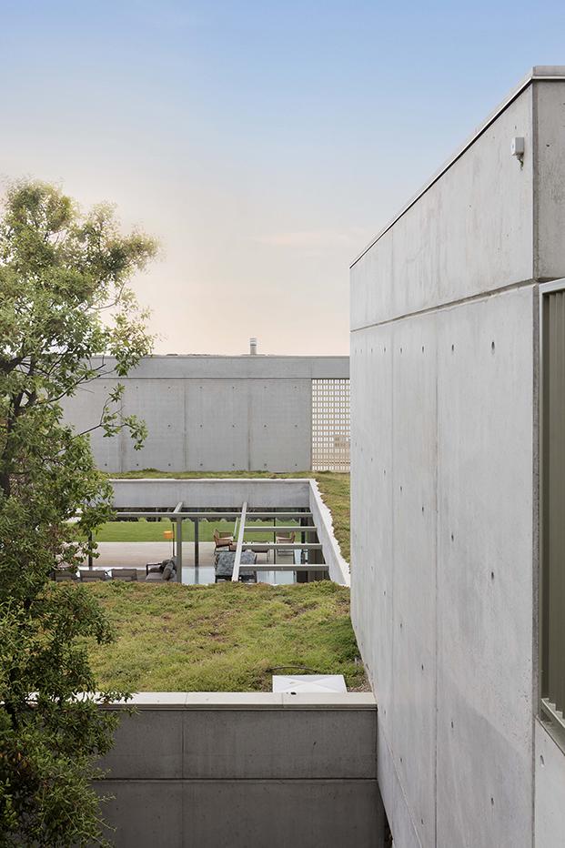 El paisajismo está pensado para suavizar la dureza y el aspecto brutalista del exterior de esta casa en la Costa Brava