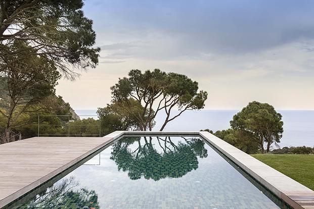 Vista de la piscina con el paisaje de la Costa Brava al fondo